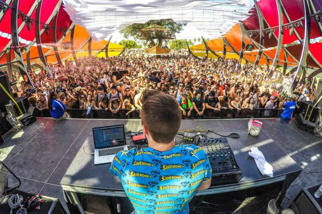 DJ Playing Festival Behind Large Crowd