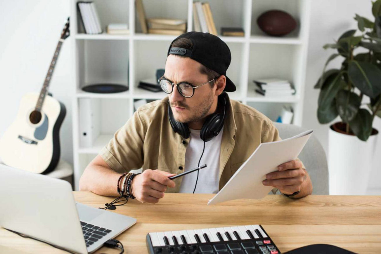 Music Producer Holding Paper Looking at Laptop