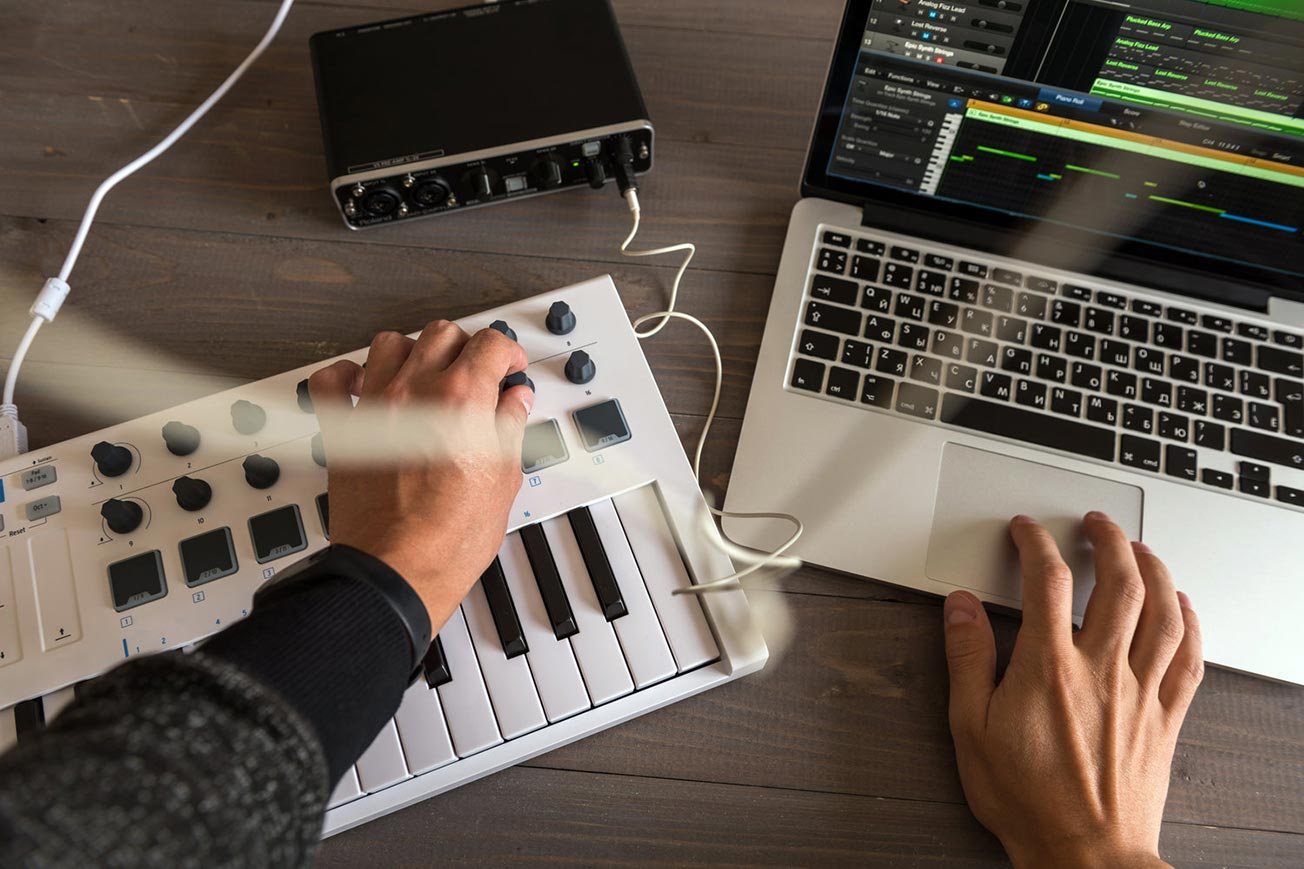 Music Producer Making Music with Midi Keyboard and Laptop - Music Program
